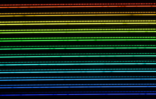 A HARPS Laser Frequency Comb generated spectrum. The horizontal lines are spectral orders (each has two separated fibres, one fed by starlight, the other by A frequency comb combs). The colour reflects the covered spectral range, from short wavelengths (blue) to long ones (red). Each horizontal line corresponds to a diffraction order and is generated and it is composed of thousands of separated, single emission peaks, whose frequency is known with very high accuracy, and are stable over long times. LFC are the next generation of 'rulers' to measure precise radial velocities.